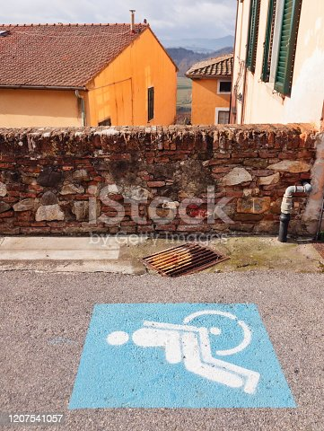 blue and white disabled-parking sign painted on the asphalt in Italy