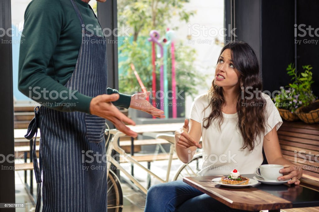 Disagreement between a waiter and a customer stock photo