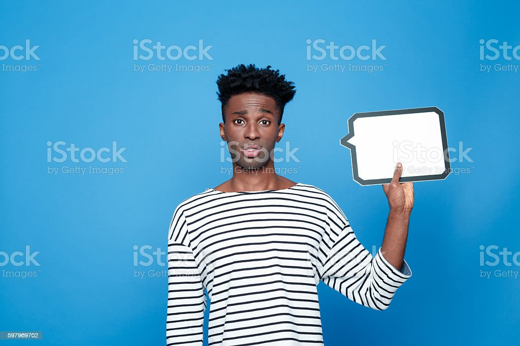 Disappointed afro american guy holding speech bubble Portrait of disappointed afro american young man wearing striped top, holding speech bubble in hand and looking at camera. Studio portrait, blue background. Adult Stock Photo