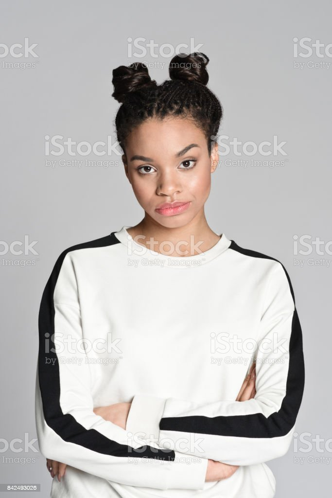 Disappointed afro american teenager woman Studio portrait of disappointed afro american teenage woman looking at camera. Studio shot, grey background. 18-19 Years Stock Photo