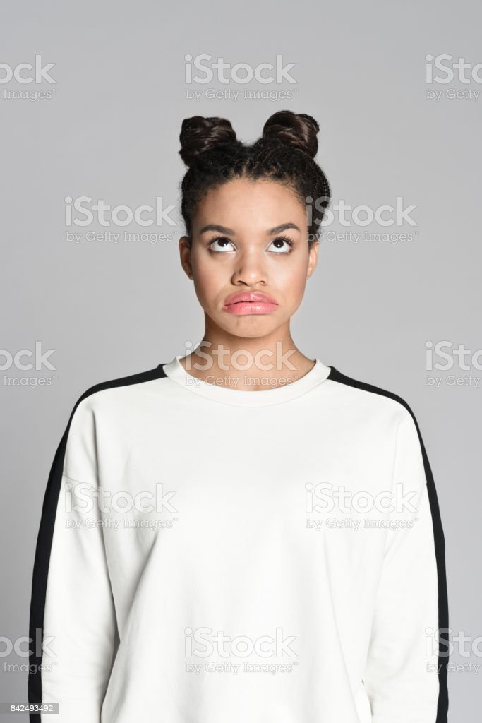 Disappointed afro american teenager woman Studio portrait of disappointed afro american teenage woman looking up. Studio shot, grey background. 18-19 Years Stock Photo