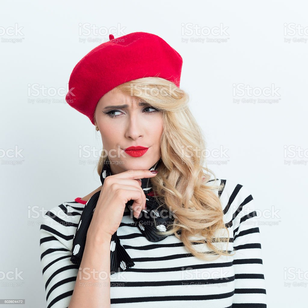 Disappointed blonde french woman wearing red beret Portrait of disappointed blonde woman in french outfit, wearing a red beret, striped blouse and neckerchief, looking away with hand on chin. Adult Stock Photo