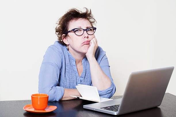 Disappointed business woman sitting at the table before a laptop stock photo