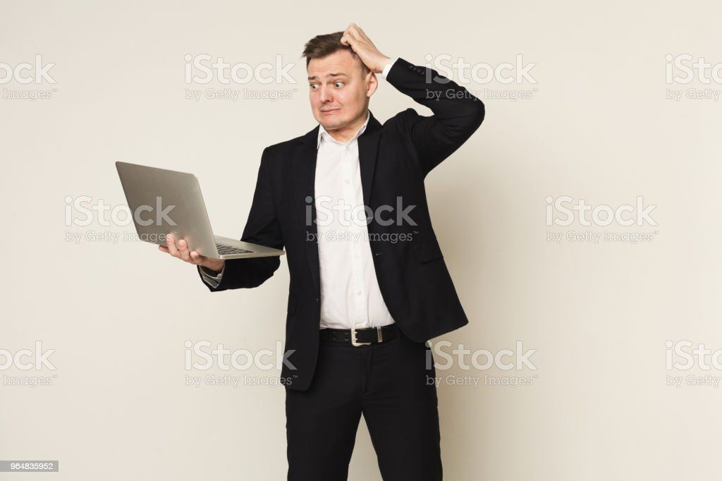 Disappointed caucasian businessman using laptop royalty-free stock photo