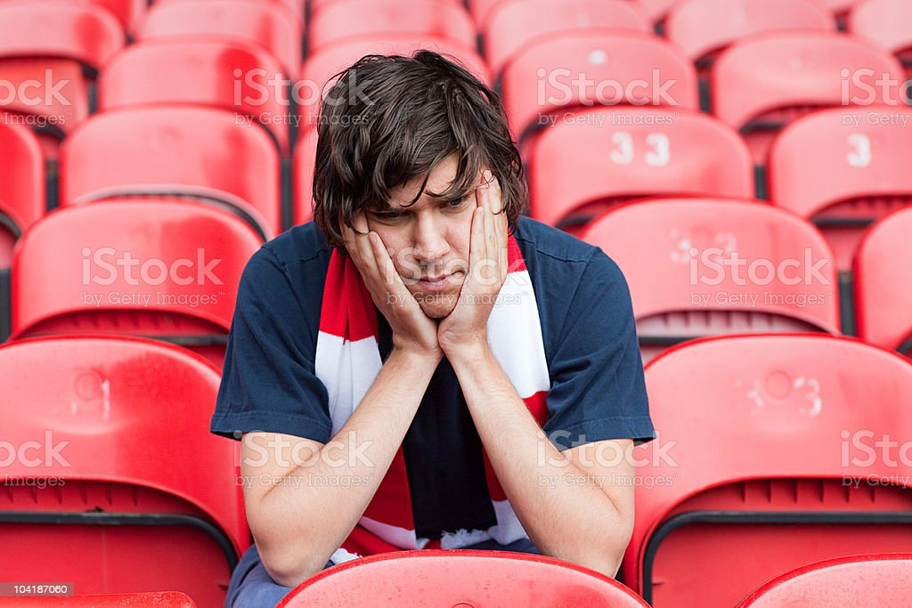 Disappointed football fan in empty stadium stock photo