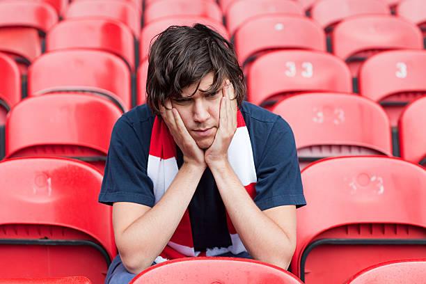 traurig-football-fan in leeren stadion - niederlage stock-fotos und bilder