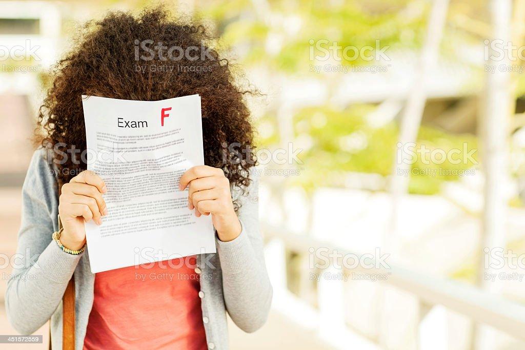 Enttäuscht Mädchen Holding Ergebnis vor Gesicht auf dem Campus – Foto