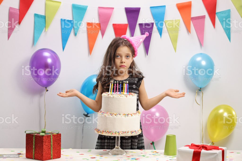 Disappointed girl with a birthday cake stock photo