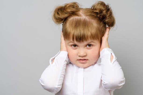 disappointed little girl covering her ears isolated - covering ears stock photos and pictures
