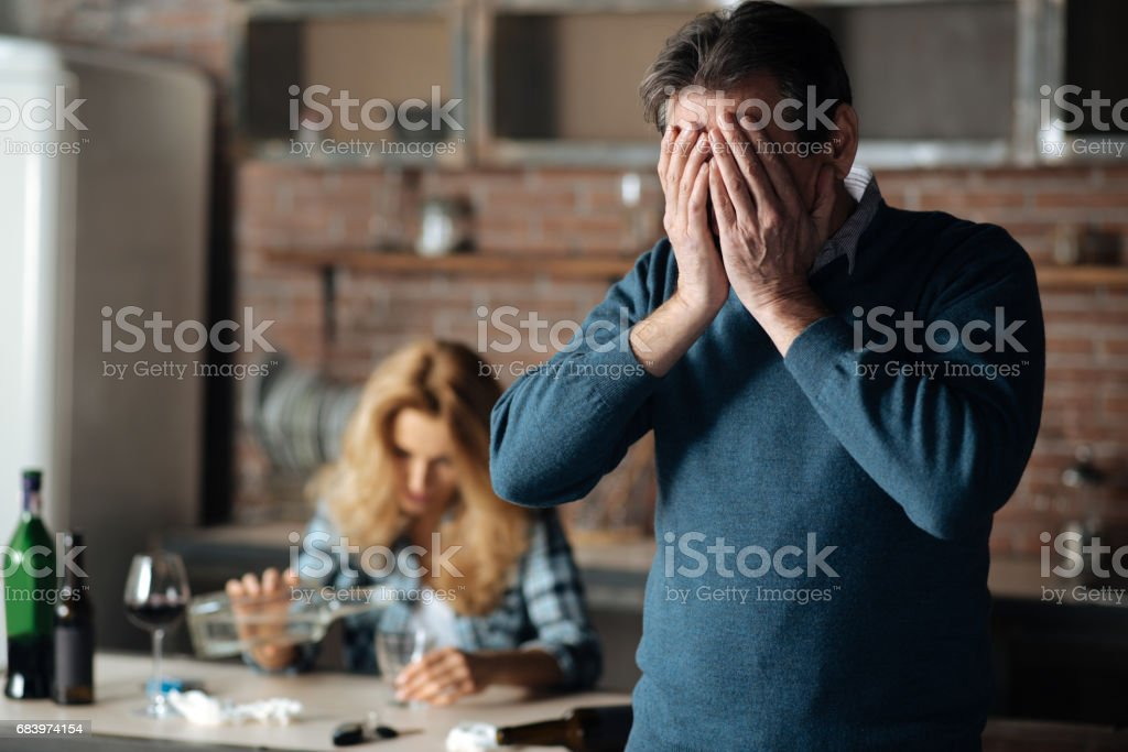 Disappointed male person covering his face stock photo