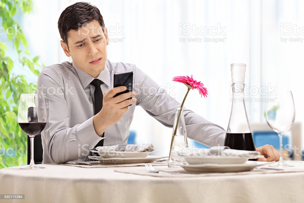 Disappointed man sitting at a restaurant stock photo