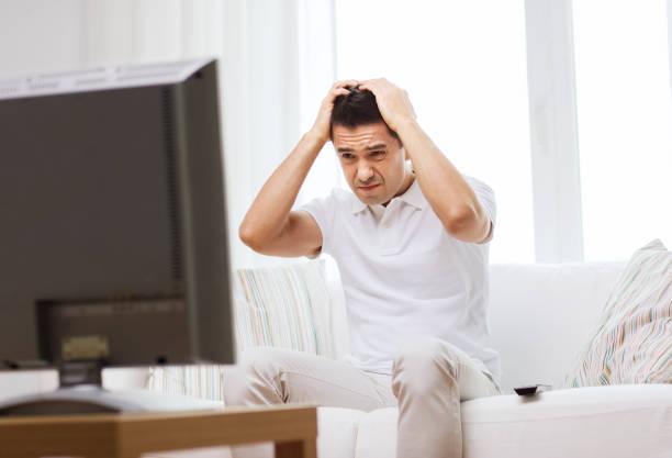 enttäuschter Mann, der zu Hause fernsehen wird – Foto