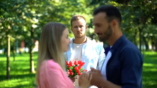 Disappointed man with flowers looking at girlfriend flirting with another man Disappointed man with flowers looking at girlfriend flirting with another man former stock pictures, royalty-free photos & images