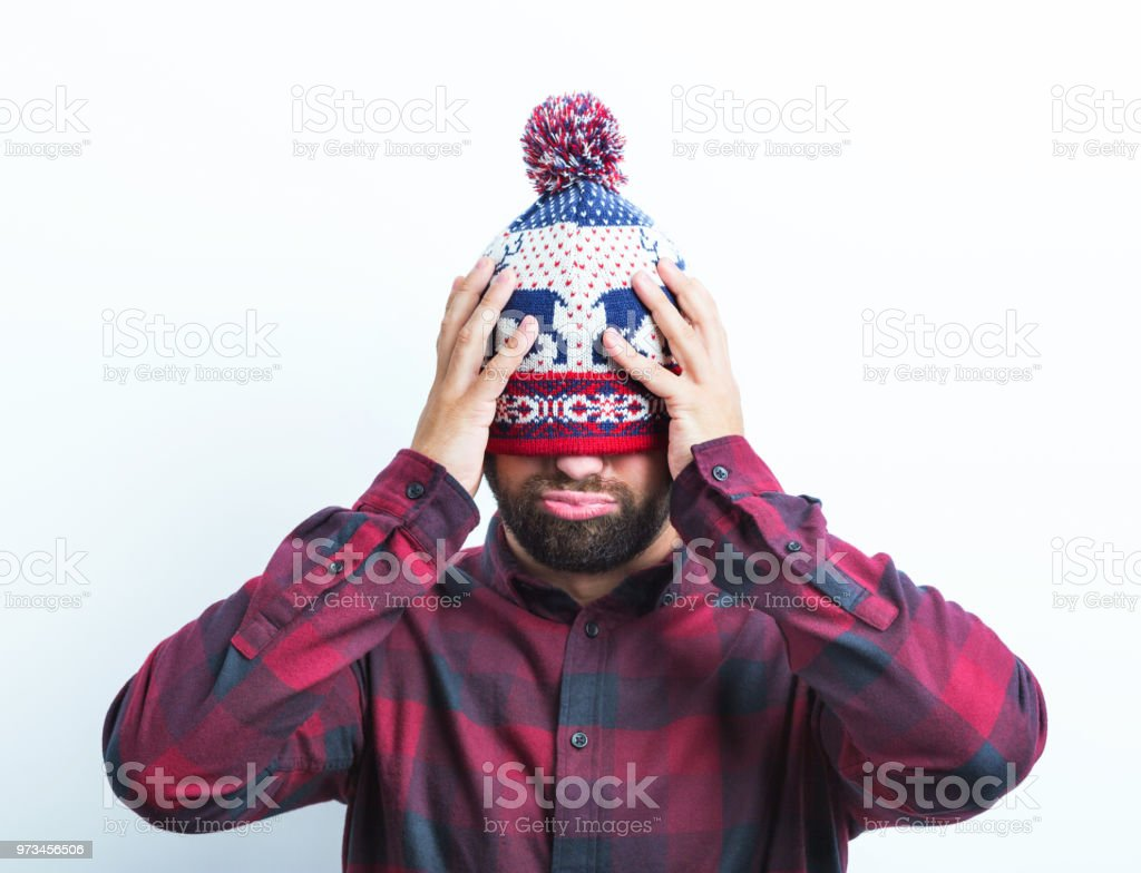 Disappointed man with winter cap Portrait of man in winter cap looking upset holding his head on white background Adult Stock Photo