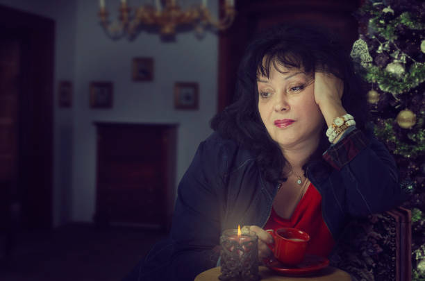 Disappointed mature woman drinking coffee at Christmas stock photo