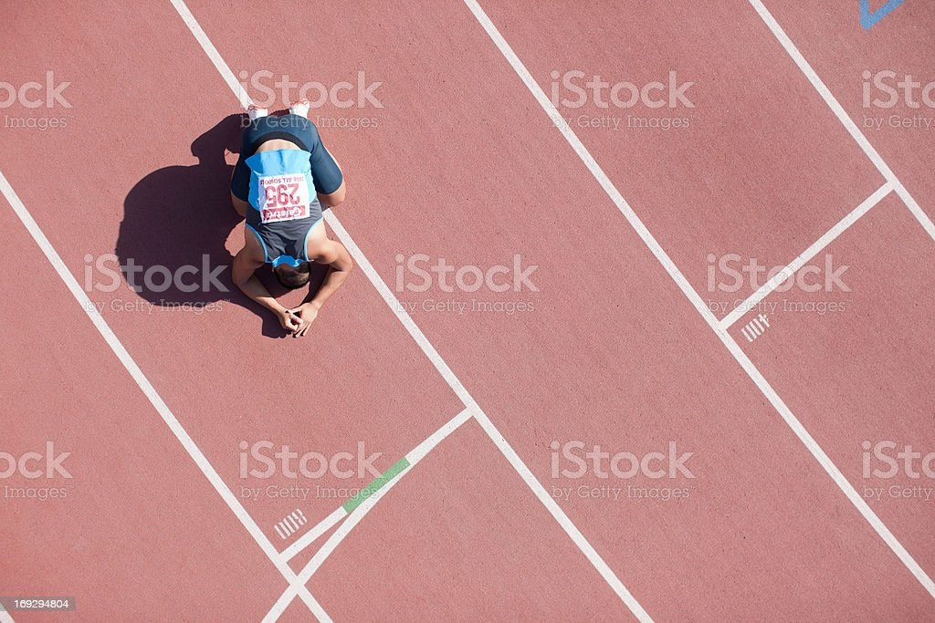 Disappointed runner kneeling on track stock photo