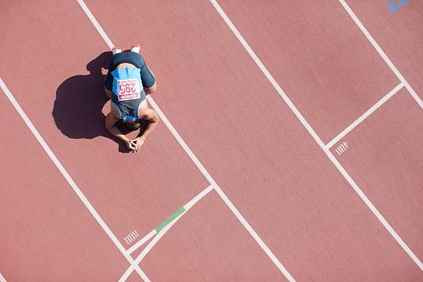 Déçu coureur kneeling sur piste - Photo
