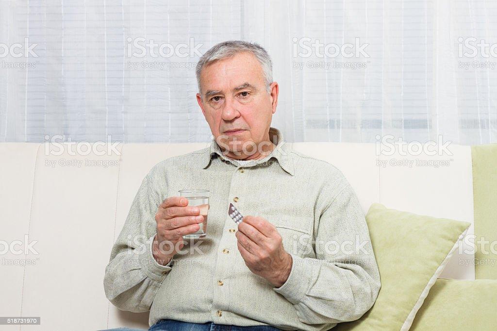 Disappointed senior man taking pills stock photo