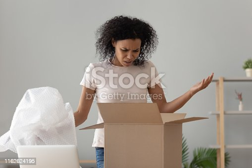 istock Disappointed shocked african woman open cardboard box receive bad parcel 1162624195