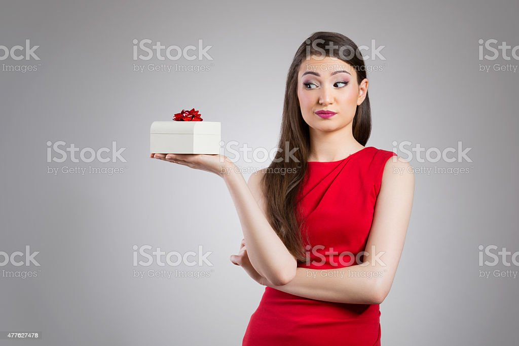 Disappointed woman holding missed gift stock photo