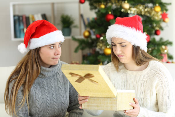 Disappointed woman receiving a gift in christmas Disappointed woman receiving a gift from a frustrated friend in christmas at home derelict stock pictures, royalty-free photos & images