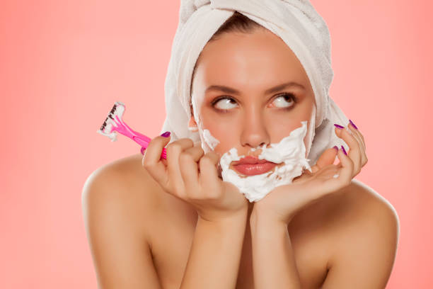 disappointed woman with foam on the face and a razor stock photo