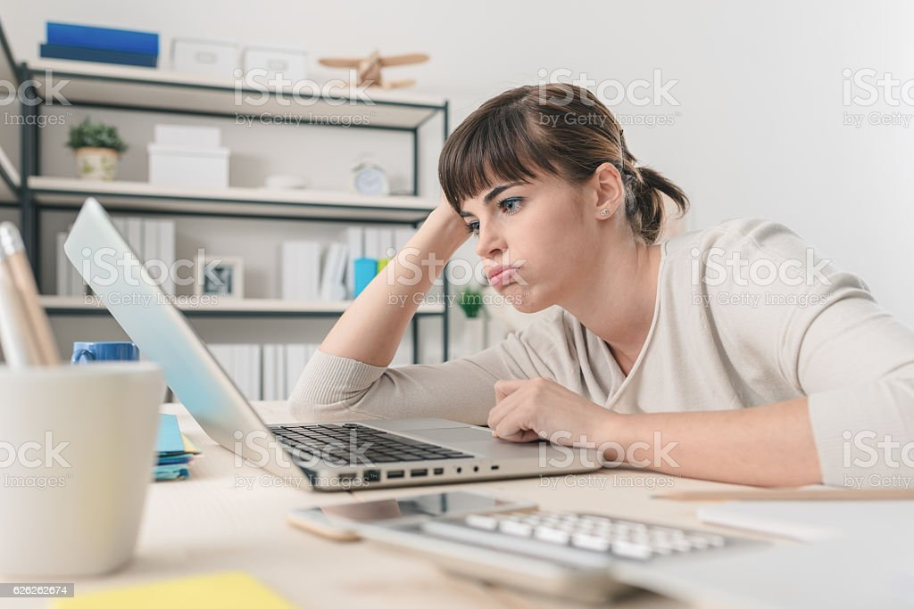 Disappointed woman working with a laptop stock photo