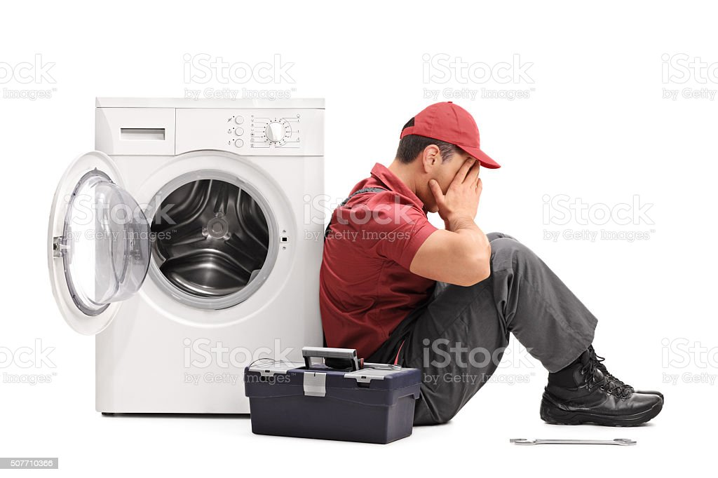 Disappointed worker sitting by a washing machine stock photo