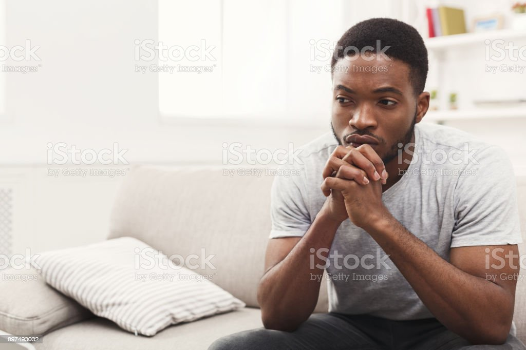 Disappointed young african-american man at home