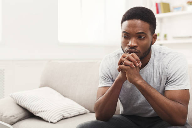 disappointed young african-american man at home - disappointment stock pictures, royalty-free photos & images