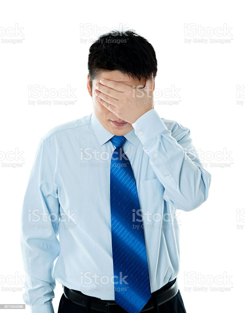 Disappointed young businessman covering eyes with hand photo libre de droits