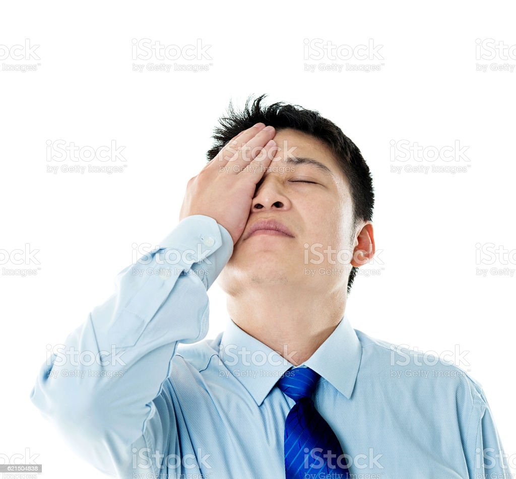 Disappointed young businessman covering eyes with hand foto stock royalty-free