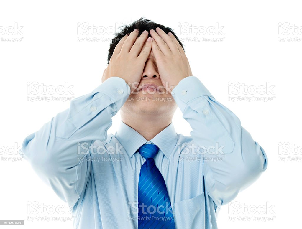 Disappointed young businessman covering eyes with hands photo libre de droits
