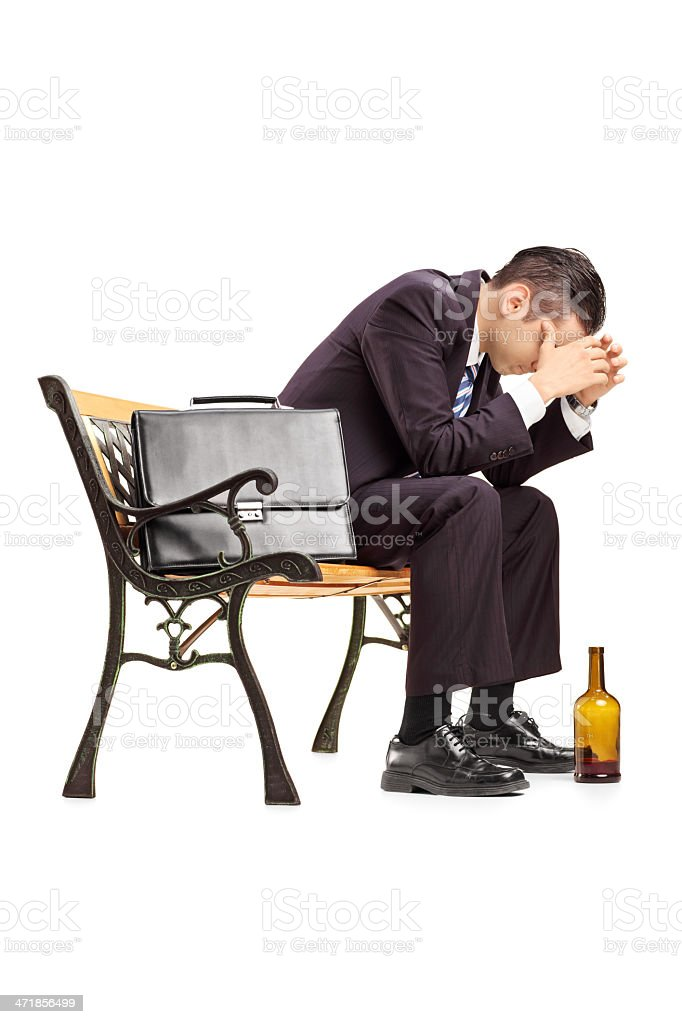Disappointed young businessperson sitting on a bench royalty-free stock photo