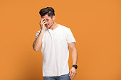 Disappointed young man on yellow background.