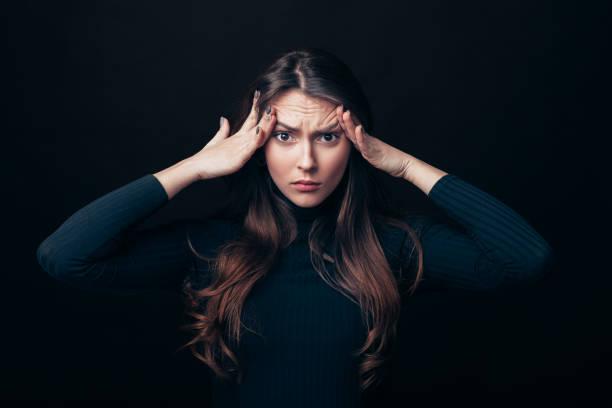 Decepción estresada mujer tocando cabeza aislada sobre fondo negro - foto de stock