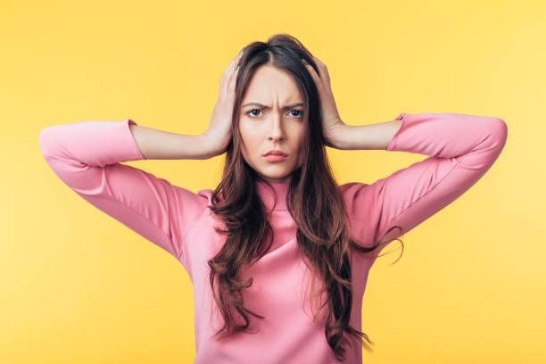 Enttäuschung gestresste Frau mit Kopfschmerzen auf gelbem Hintergrund isoliert – Foto