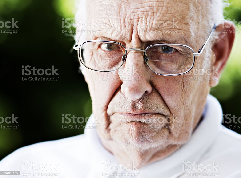 Disapproving old man glares at camera over his glasses, frowning stock photo