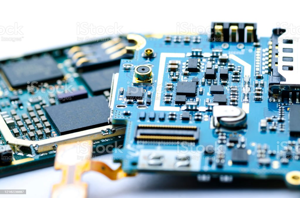Disassembled electronic boards with chips, electronic components and precious metals for recycling Disassembled electronic boards with chips, electronic components and precious metals for recycling, close-up, soft focus Blue Stock Photo
