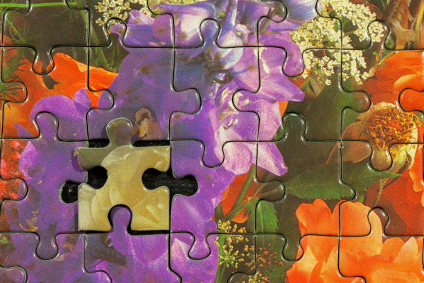 Disassembled puzzle with a last wrong piece impossible to fill stock photo