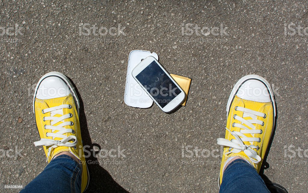 Disassembled smartphone on the ground in front of person stock photo