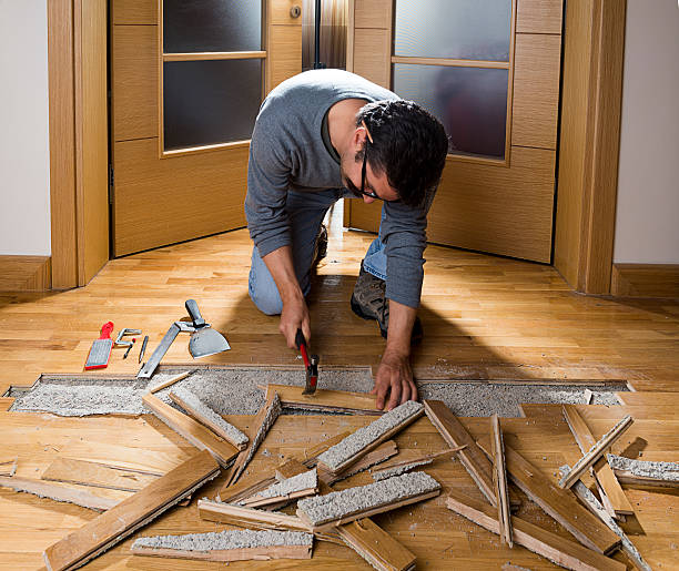 Disassembling Ruined Parquet Manual worker disassembling wooden floor ruined from moisture and water leak.   detach stock pictures, royalty-free photos & images