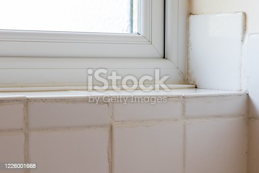 DIY disaster. Bad tiling of ceramic bathroom tiles. Terrible fixing and grouting around a window. Do-it-yourself fail by amateur handyman or rogue trader,