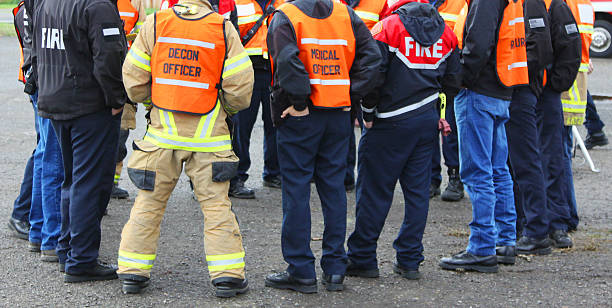 Disaster Team Discussion Circle In any urban area the fire departments and emergency response teams will conduct disaster preparedness drills. This group of team members gathers around to discuss options. accidents and disasters stock pictures, royalty-free photos & images