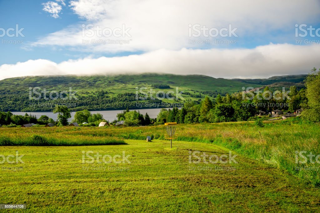 A disc golf basket at the end of the hole with a scenic view to Loch Tay and background hills, central Scotland stock photo