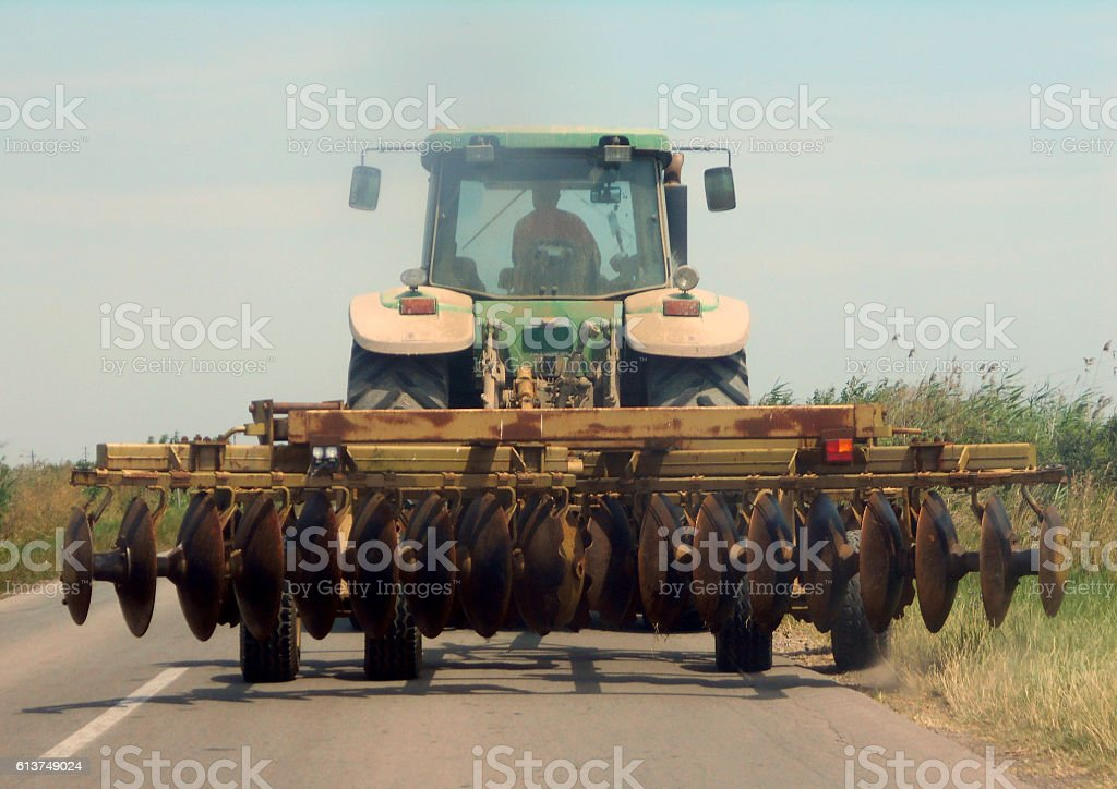 disc harrow behind the tractor wider than the road stock photo