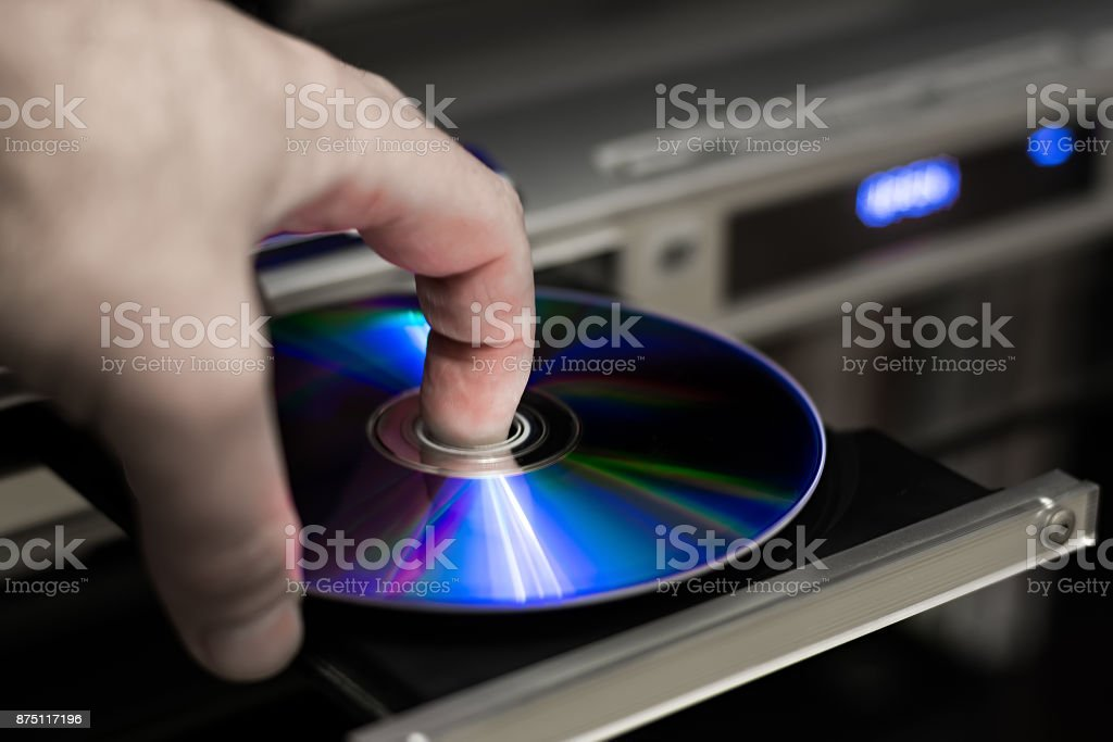 DVD disc inserting to player stock photo