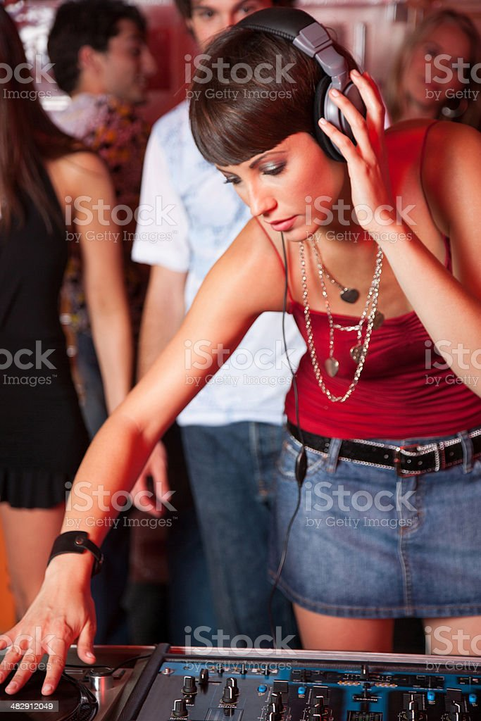 Disc jockey in nightclub with people dancing around her  stock photo