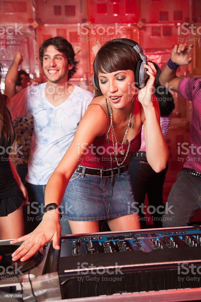 Disc jockey in nightclub with people dancing around her smiling stock photo