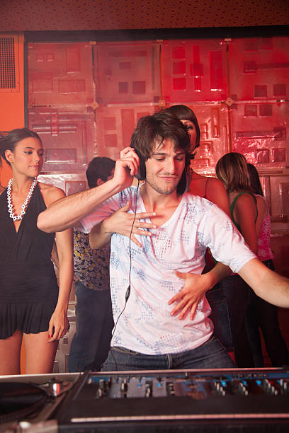 Disc jockey in nightclub with people dancing around him smiling stock photo